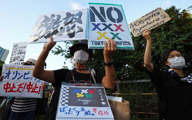 People protest against the Tokyo 2020 Olympic Games- Tokyo, Japan - July 18, 2021. Protesters hold placards during a rally near Akasaka State Guest where International Olympic Committee (IOC) President Thomas Bach attends a welcome ceremony hosted by the Japanese government. REUTERS