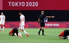 Tokyo 2020 Olympics- Football - Men - Group C - Egypt v Spain - Sapporo Dome, Sapporo, Japan - July 22, 2021. Egypt players pray at the end of the match as Pedri of Spain looks dejected REUTERS/Kim Hong-Ji