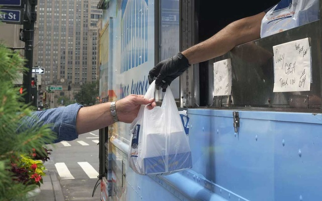A food order is up during the lunch rush at Uncle Gussy's food truck in Manhattan, July 8, 2021. For thousands of food truck operators and cart vendors in New York, the ability to make meaningful profits depends on large numbers of workers returning to the office. (John Taggart/The New York Times)