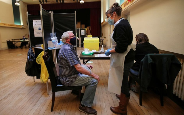 A healthcare worker speaks with an elderly person before administering a dose of the Pfizer-BioNTech COVID-19 vaccine at Thornton Little Theatre managed by Wyre Council in Lancashire, Britain January 29, 2021. REUTERS
