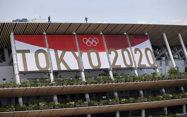 Tokyo 2020 Olympics - Arrival Ceremony for Tokyo 2020 Olympic Torch Relay - Shinjuku City, Tokyo, Japan - July 23, 2021 Man walks atop the Olympic Stadium. REUTERS
