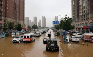 Men stand on a vehicle on a flooded road following heavy rainfall in Zhengzhou, Henan province, China July 23, 2021. Reuters