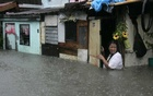 A woman wades in floodwaters brought by monsoon rain, intensified by tropical storm Trami, in Kawit town of Cavite city, south of Manila August 19, 2013. REUTERS