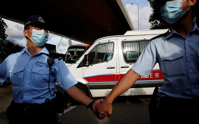 FILE PHOTO: Police officers escort a prison van which is carrying Tong Ying-kit, the first person charged under the new national security law, as he leaves West Kowloon Magistrates' Courts, in Hong Kong, China July 6, 2020. REUTERS/Tyrone Siu/File Photo