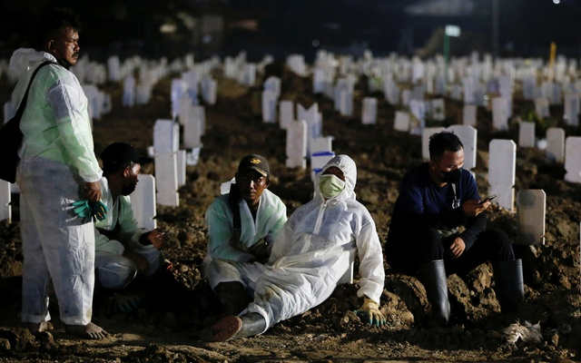Workers wearing Personal Protective Equipment (PPE) take a break while burying the coronavirus disease (COVID-19) victims in Jakarta, Indonesia, July 23, 2021. Reuters