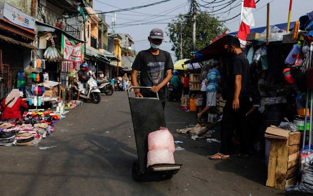 A man wearing a protective mask pushes a trolley at a traditional market amid the coronavirus disease (COVID-19) outbreak, in Jakarta, Indonesia, July 24, 2021. REUTERS