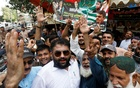Supporters of political parties react to the media as they chant slogans outside a polling station during voting to elect lawmakers for legislative assembly in Pakistan-administered Kashmir, in Karachi, Pakistan July 25, 2021. REUTERS/Akhtar Soomro