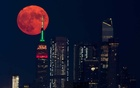 The full moon rises behind the Empire State Building in New York City, New York, US, July 23, 2021. REUTERS