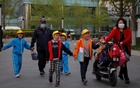 People pick up children from a school in Beijing, China, April 6, 2021. REUTERS