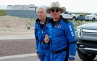 Billionaire American businessman Jeff Bezos walks with crewmate Wally Funk at the landing pad after they flew on Blue Origin's inaugural flight to the edge of space, in the nearby town of Van Horn, Texas, US July 20, 2021. REUTERS