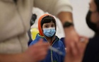 A child looks on as a woman receives a dose of Pfizer/BioNTech coronavirus disease (COVID-19) vaccine during a vaccination campaign inside the University of Santiago, Chile June 30, 2021. Reuters