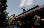A girl holds a pipe as she stands on a container filled with drinking water from a municipal water tanker on a hot summer day in New Delhi, India, Jul 6, 2021. REUTERS