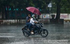 A pillion rider uses an umbrella to protect himself and the motorcyclist from the rain on the Dhaka University campus on Tuesday, Jul 27, 2021. Photo: Mahmud Zaman Ovi