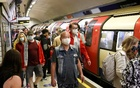 People wearing protective face masks walk along a platform on the London Underground, amid the coronavirus disease (COVID-19) outbreak, in London, Britain, Jul 25, 2021. REUTERS
