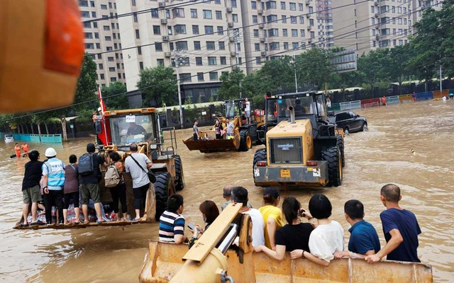 People ride on front loaders as they make their way through a flooded road following heavy rainfall in Zhengzhou, Henan province, China July 23, 2021. REUTERS