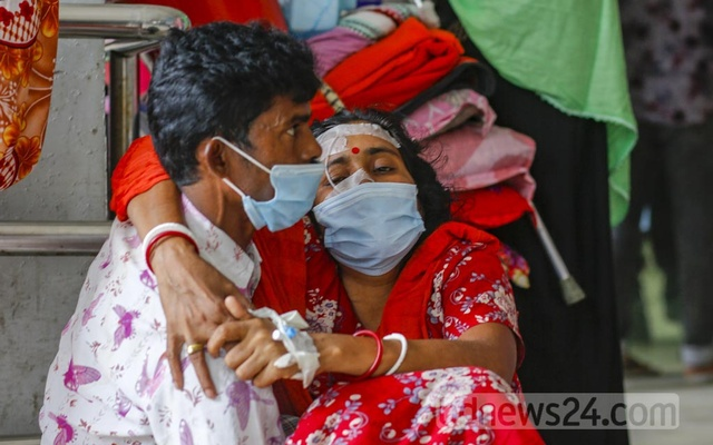 Husband carries suspected coronavirus patient Shipra, who gave a single name and also has typhoid, into Dhaka Medical College Hospital as they arrive from Bogura on Wednesday, Jul 28, 2021. Photo: Mahmud Zaman Ovi