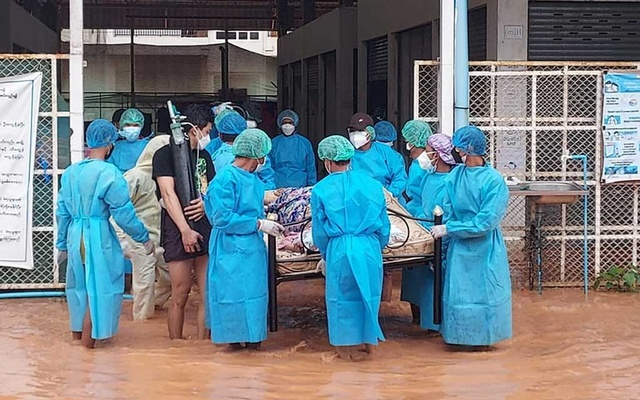 Volunteers in protective suits carry a COVID-19 patient lying on a hospital bed as they try to relocate patients who are dependent on oxygen from the COVID-19 centre due to the flood in Myawaddy, Karen state, Myanmar, July 26, 2021. Karen Information Centre via REUTERS