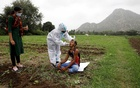Healthcare worker Hemaben Raval collects a swab for a rapid antigen test from farmer Vinod Vajabhai Dabhi in his field, during a door-to-door vaccination drive amid the ongoing coronavirus disease (COVID-19) outbreak in Banaskantha district in the western state of Gujarat, India, July 23, 2021. REUTERS