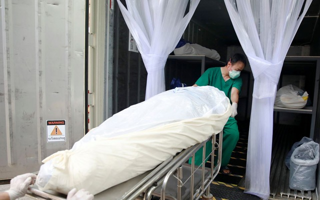 Health care workers move a dead body to a container after a hospital morgue overwhelmed by COVID-19 deaths begun to store bodies in refrigerated containers, as the country struggles to deal with its biggest outbreak to date, in Pathum Thani, Thailand July 31, 2021. REUTERS/Soe Zeya Tun