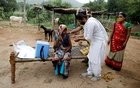 FILE PHOTO: Healthcare worker Jankhana Prajapati gives a dose of the domestically manufactured COVISHIELD vaccine to villager Amiyaben Dabhi during a door-to-door vaccination drive in Banaskantha district in the western state of Gujarat, India, July 23, 2021. REUTERS/Amit Dave/File Photo