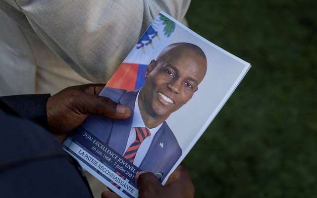A person holds a photo of late Haitian President Jovenel Moise, who was shot dead earlier this month, during his funeral at his family home in Cap-Haitien, Haiti, July 23, 2021. REUTERS