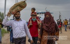 A man walks carrying his toddler girl on his shoulders from Shimulia ferry terminal in Munshiganj on Saturday, Jul 31, 2021 amid growing pressure of travellers with factories set to reopen amid the coronavirus lockdown. Photo: Mahmud Zaman Ovi
