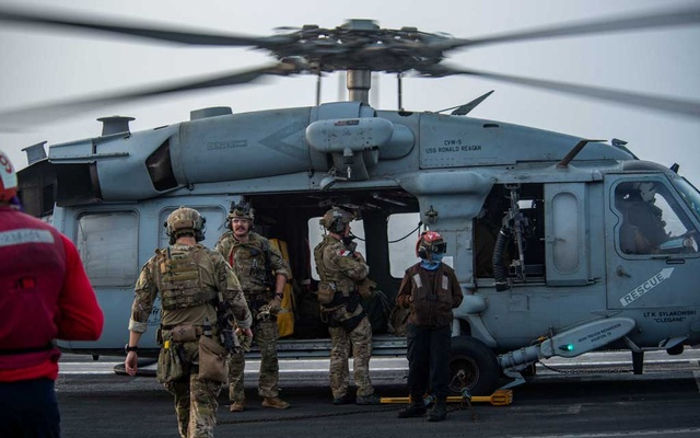 Sailors assigned to Explosive Ordnance Disposal Mobile Unit (EODMU) 5 board an MH-60S Sea Hawk helicopter, attached to the