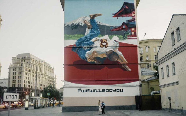 A mural in Moscow shows a martial arts practitioner with a bear emblem flipping a rival wearing the initials of WADA, the World Anti-Doping Agency, on Saturday, July 31, 2021. The New York Times