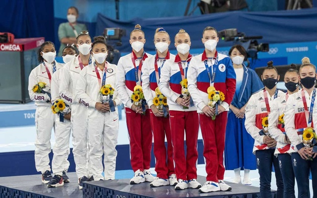 The US women's team on the podium stand together after the women's gymnastics final at the delayed Tokyo 2020 Olympic Games in Tokyo on Tuesday, July 27, 2021. Russia, centre, finished more than 3 points ahead of the US to win gold and Great Britain won the bronze medal. The New York Times