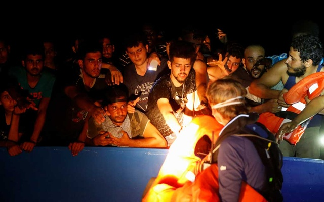 A RHIB (rigid hulled inflatable boat) crew member from the German NGO migrant rescue ship Sea-Watch 3 distributes life jackets to migrants on an overcrowded wooden boat during a rescue operation in international waters off the coast of Tunisia, in the western Mediterranean Sea, August 1, 2021. Reuters