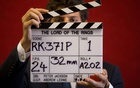 A gallery assistant poses for a photograph with a clapper board used in the filming of the Lord of the Rings film 'Return of the King' in Bonhams auction house in London July 31, 2014. REUTERS/Neil Hal