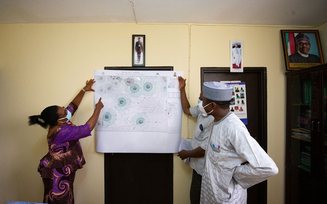 An undated handout photo shows health officials examining a GRID3 map for Kuje, Nigeria. Governments and organizations around the world are using geospatial data and digital mapping tools to guide their vaccination campaigns. (GRID3 via The New York Times)