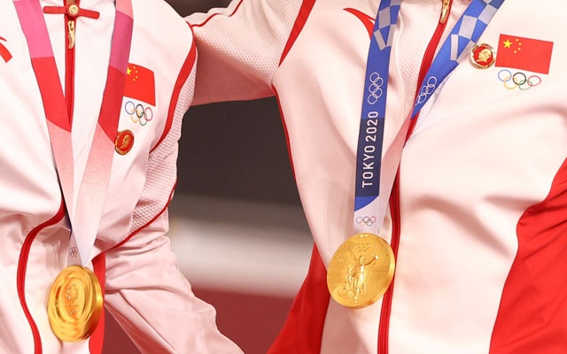 Gold medallists Bao Shanju of China and Zhong Tianshi of China wearing protective face masks pose with badges of the late Chinese chairman Mao Zedong pinned to their tracksuits. Tokyo 2020 Olympics - Cycling - Track - Women's Team Sprint - Medal Ceremony - Izu Velodrome, Shizuoka, Japan - August 2, 2021. REUTERS