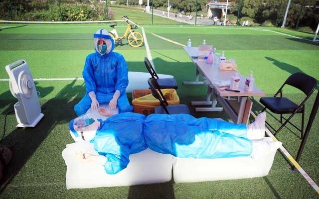 Medical workers in protective suits rest on ice blocks at a nucleic acid testing site on a field following new cases of the coronavirus disease (COVID-19) in Zhengzhou, Henan province, China August 2, 2021. China Daily via REUTERS