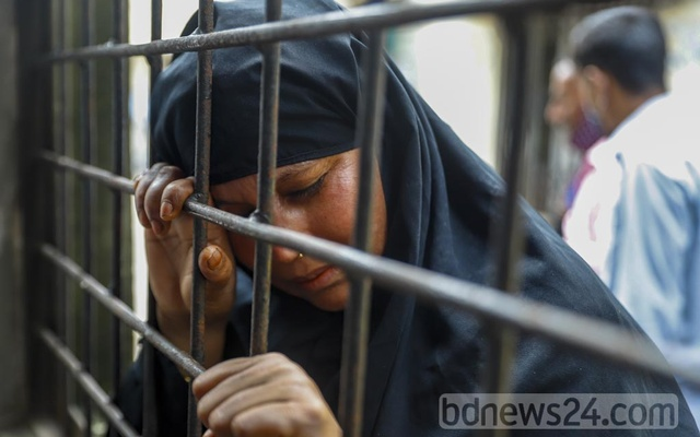 Faruki, who gave a single name, arrives at Dhaka Medical College's mortuary on Wednesday, Aug 4, 2021 to receive the remains of her sister-in-law Jahanara Begum, one of the at least 50 victims of Hashem Foods factory fire. She worked at the factory's lollipop section.