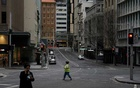 People with protective face masks walk through the quiet city centre during a lockdown to curb the spread of a coronavirus disease (COVID-19) outbreak in Sydney, Australia, July 28, 2021. REUTERS/Loren Elliott