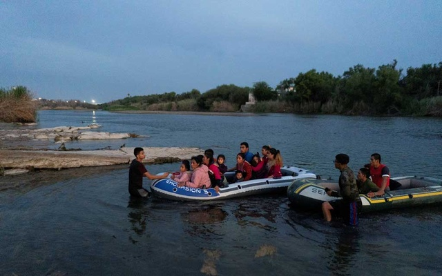 Asylum-seeking migrant families from Guatemala and Honduras arrive to the US side of the bank on an inflatable raft after crossing the Rio Grande river into the United States from Mexico in Roma, Texas, US, July 28, 2021. REUTERS