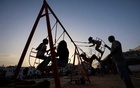 A man looks after children playing at a playground in Tunis, Tunisia July 30, 2021. Picture taken July 30, 2021. REUTERS/Ammar Awad