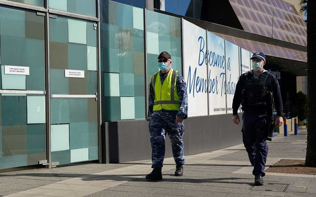 Personnel from the Australian Defence Force and New South Wales Police Force patrol a street in the Bankstown suburb during an extended lockdown to curb the spread of the coronavirus disease (COVID-19) in Sydney, Australia, August 3, 2021. REUTERS