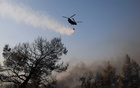 A chinook helicopter makes a water drop as a wildfire continues to rage in Varympompi suburb, north of Athens, Greece, August 4, 2021. REUTERS