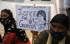 Women sit next to a placard near a crematorium where people are protesting against the alleged rape and murder of a 9-year-old girl in New Delhi, India, August 5, 2021. REUTERS/Anushree Fadnavis