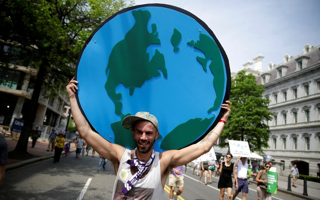 A protester carries a sign depicting the earth during the Peoples Climate March near the White House in Washington, U.S., on April 29, 2017. REUTERS