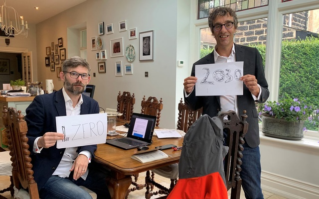 Scientists Joeri Rogelj and Piers Forster hold up signs urging reduction in carbon emissions after completing a major UN climate report, in a house in Harrogate, Britain Aug 7, 2021. Stella Forster/REUTERS
