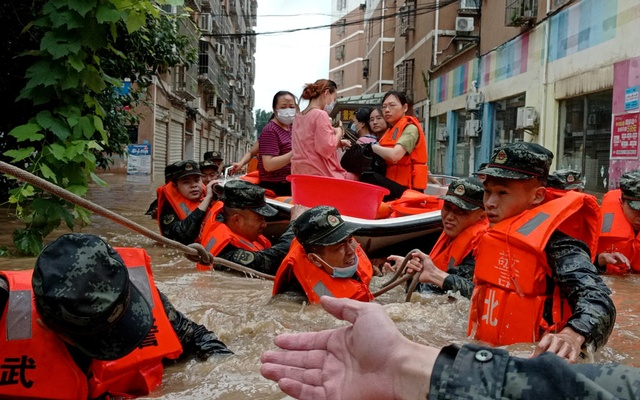 Paramilitary police officers evacuate residents stranded by floodwaters with a boat following heavy rainfall in Suizhou Hubei province, China August 12, 2021. cnsphoto via REUTERS