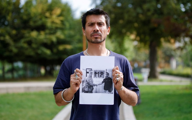 Mokhles, 35-years-old Afghan refugee, poses with a printed photo of him during his work as an interpreter for military forces in Afghanistan, during an interview with Reuters in Paris, France, August 16, 2021. REUTERS.