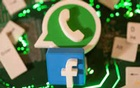 3D printed Facebook and WhatsApp logos and keyboard buttons are placed on a computer motherboard in this illustration taken January 21, 2021.Reuters