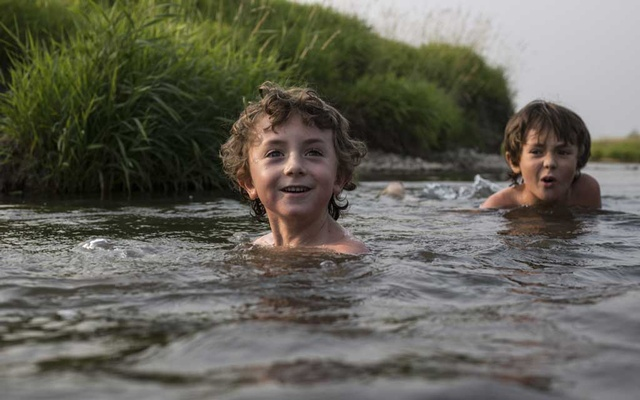 Soren Johnson, 6, and his older brother Killian, 8, swim in Jackknife Creek at their home in Freedom, Wyo, Aug 8, 2021. The New York Times
