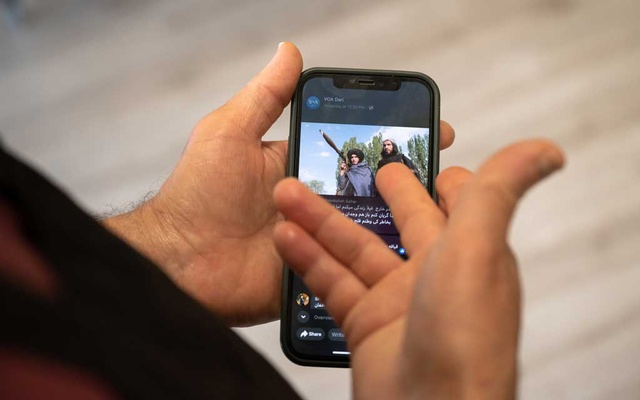 A photograph made as the Taliban took control of Kabul is displayed on Ho Karimi's phone in Fremont, Calif, on Monday, Aug 16, 2021. Tens of millions of Afghans now have mobile phones, connecting them with the outside world in ways that were impossible when the Taliban last ruled. (Mike Kai Chen/The New York Times)