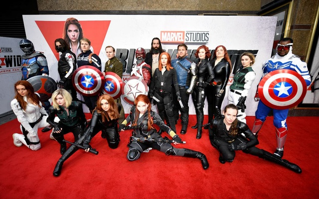 Fans dressed as Avengers characters pose for a picture during a special fan event for the Marvel film