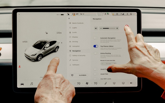 FILE — A couple demonstrates some of the options and capabilities that are accessible via the touch-screen of their Tesla automobile in Chicago, June 4, 2021. As federal investigators escalate their scrutiny of Tesla's driver-assistance technology, another problem is emerging for the electric carmaker: complaints among customers that they have been sold an additional driver-assistance option that doesn't operate as advertised. (Evan Jenkins/The New York Times)